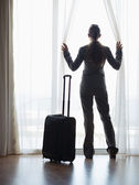 Silhouette of business woman with wheel bag looking into hotel window — Stock Photo