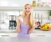 Ragazza adolescente felice mangiare muffin al cioccolato con latte — Foto Stock