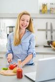 Dospívající dívka dělat sendvič v kuchyni a při pohledu na laptop — Stock fotografie