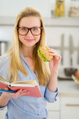 Happy teenager girl eating sandwich and reading book — Stock Photo