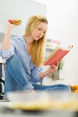 Young woman studying in kitchen — Stock Photo