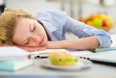Teenage girl fall asleep while studying in kitchen — Stock Photo