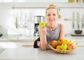 Gelukkig jonge huisvrouw met apple in moderne keuken — Stockfoto