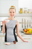 Happy young housewife drinking coffee with chocolate muffin — Stock Photo