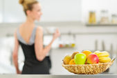 Closeup on plate of fruits and young housewife in background — Stock Photo