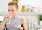 Young housewife eating pills and drinking water — Stock Photo
