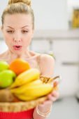 Surprised teenage girl holding plate of fruits — Stock Photo