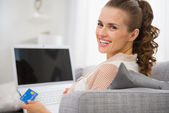 Smiling young housewife with laptop and credit card — Stock Photo