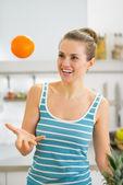 Felice giovane donna gettando arancione in cucina — Foto Stock