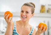 Donna giovane sorridente, mostrando le arance in cucina — Foto Stock