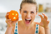 Young woman scaring with orange with hallowing face — Stock Photo