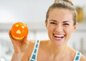 Smiling young woman showing orange with funny face — Stock Photo