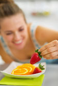 Closeup on happy young woman decorating plate with fruits — Stock Photo