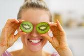 快乐的年轻女人,使眼睛与猕猴桃切片 — 图库照片