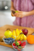 Closeup on fruits on cutting board and young housewife — Stock Photo