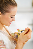 Heureuse jeune femme manger salade de fruits — Photo
