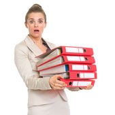 Surprised business woman holding stack of folders — Stock Photo