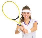 Smiling tennis player showing racket — Stock Photo