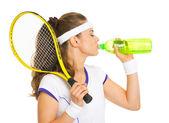 Kvinnlig tennis spelare dricksvatten — Stockfoto