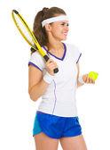 Jugadora de tenis con raqueta y pelota mirando sonriente — Foto de Stock