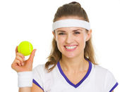 Happy female tennis player showing tennis ball — Stock Photo
