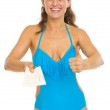 Happy young woman in swimsuit showing air tickets and thumbs up — Stock Photo #27521399