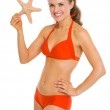 Portrait of smiling young woman in swimsuit starfish — Stock Photo #27521751