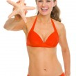 Smiling young woman in swimsuit showing starfish — Stock Photo