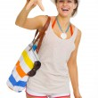 Smiling young woman with beach bag showing starfish — Stock Photo #27522507