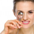 Beauty portrait of happy young woman using eyelash curler — Stock Photo