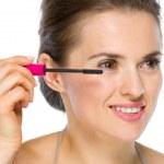 Beauty portrait of happy young woman applying mascara — Stock Photo