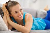Mutlu genç kadın oturma odasında kanepede döşenmesi — Stok fotoğraf