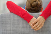 Closeup on hands of young woman laying on divan in living room. — Stock Photo