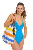Portret szczęśliwy młoda kobieta w strój kąpielowy i plaża torba — Zdjęcie stockowe