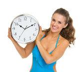 Mulher jovem feliz no relógio mostrando de maiô — Foto Stock
