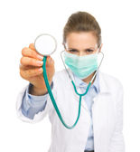 Closeup su stetoscopio in mano del medico donna in maschera — Foto Stock