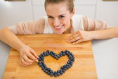 Happy young housewife making heart with blueberries — Stock Photo