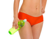 Closeup on bottle of water in hand of young woman in swimsuit — Stock Photo