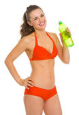 Smiling young woman in swimsuit with bottle of water — Stok fotoğraf