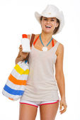 Happy young woman with beach bag showing sun screen creme — Stock Photo