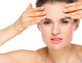 Beauty portrait of concerned young woman checking facial skin — Stock Photo