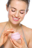 Beauty portrait of happy young woman with creme — Stock Photo