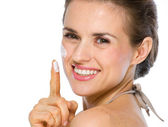 Beauty portrait of happy young woman showing creme on finger — Stock Photo