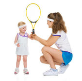 Mother giving baby tennis racket — Stock Photo