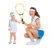 Happy mother and baby holding tennis racket — Stock Photo