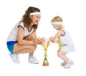 Mutter und baby im tennis kleidung mit medaille und pokal — Stockfoto