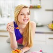 Smiling young woman eating fruits salad in kitchen — Stock Photo #30043883