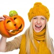 Young womin hat and scarf scaring with jack-o-lantern — Stock Photo #30044095
