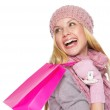 Smiling teenager girl in winter hat and scarf with shopping bag — Stock Photo #30044761