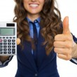 Closeup on smiling business woman showing calculator and thumbs  — Stock Photo